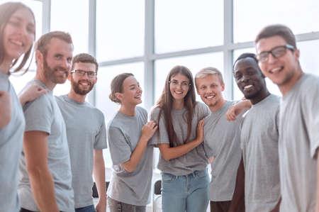 Gruppe verschiedener junger Männer in grauen T-Shirts, die zusammenstehen