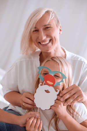 close up. mother dressing daughter merry mask. Фото со стока