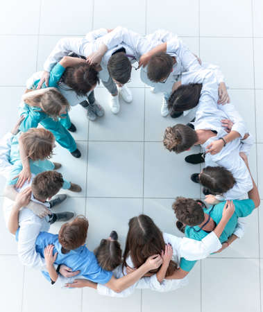 young woman doctor standing in front of her happy colleagues Stock Photo