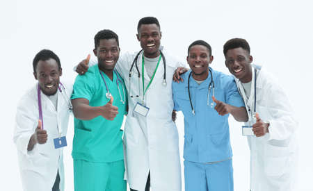 smiling interns doctors giving thumbs up. isolated on white Imagens