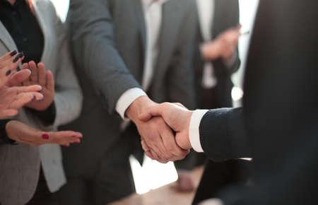 ścieśniać. uśmiechnięty biznesmen uścisk dłoni ze swoim partnerem biznesowym