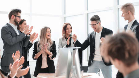 boss and happy employees applaud standing in the office