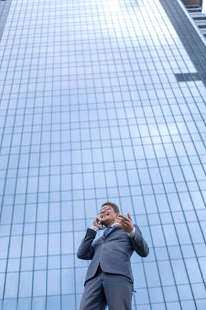 happy business man with smartphone standing in front of high rise office building