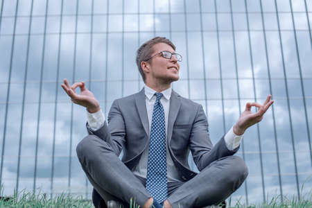 businessman in Lotus pose sitting on grass in front of office building Stok Fotoğraf