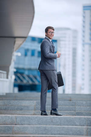 smiling business man climbing the steps to the business center Reklamní fotografie