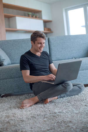 young man typing on his laptop in cozy living room