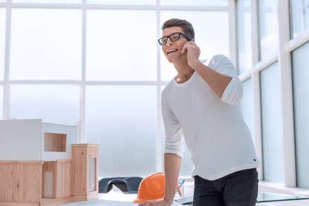 successful designer talking on his smartphone in design Studio.
