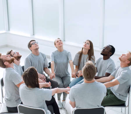 group of concentrated people sitting in a circle. Stock Photo