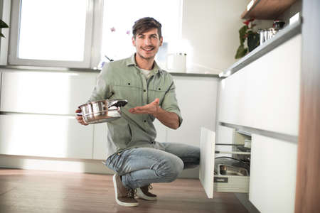 young man looking at clean dishes in dishwasher Stockfoto