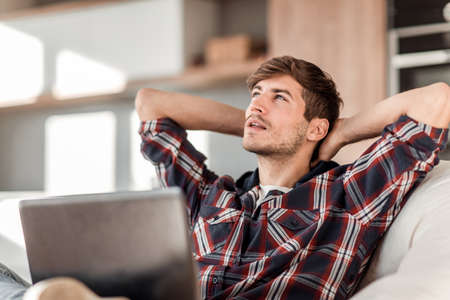 close up. dreaming young man sitting in front of an open laptop