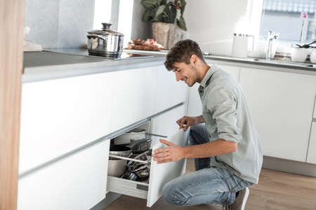 young man sitting near the dishwasher in his kitchen