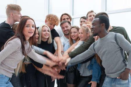 divers jeunes mettant leurs mains ensemble