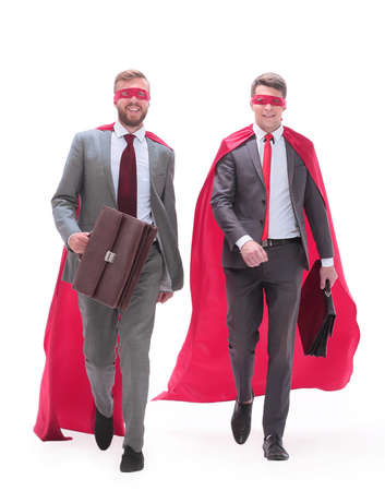 business partners in superhero capes walking together. Stock Photo