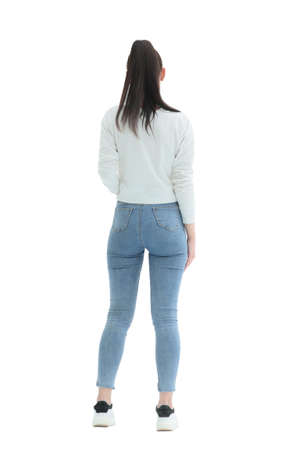 rear view. stylish girl in jeans standing in front of a white wall. isolated on white