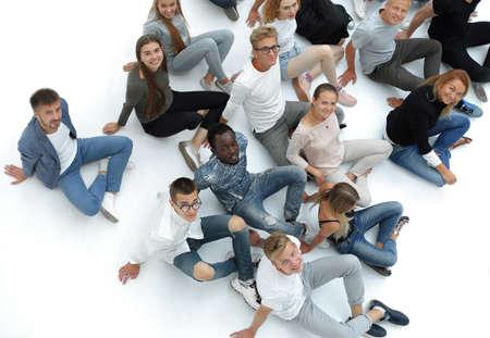 Gruppe junger Leute, die auf dem Boden sitzen und in die Kamera schauen. Standard-Bild