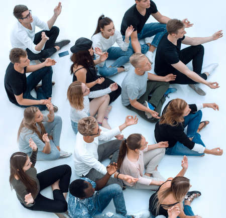 group of diverse young people meditate sitting on the floor. Standard-Bild