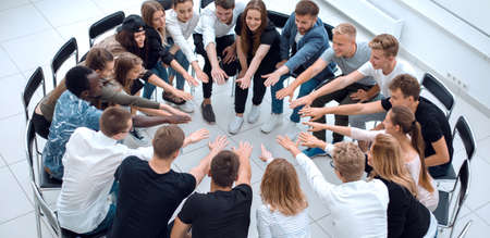 group of diverse young people putting their hands togethe