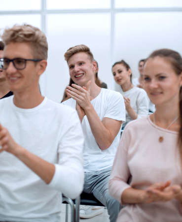 group of young people applaud at a group meeting