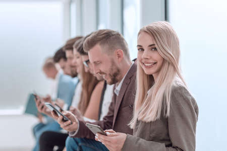 young business people with smartphones sitting in office corridor.
