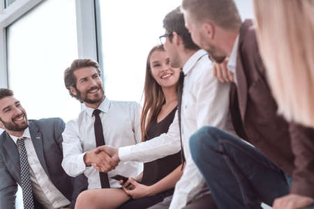 young business people shaking hands while sitting in the office lobby