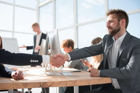 business colleagues shaking hands with each other at the meeting.