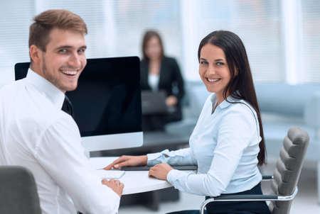 członkowie zespołu biznesowego siedząc przy biurku i patrząc na kamery. Zdjęcie Seryjne