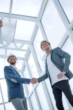 architects and engineers shaking hands in a new building.