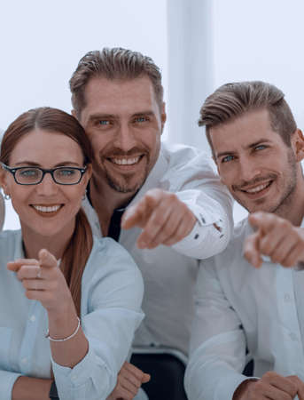 smiling business team pointing at you