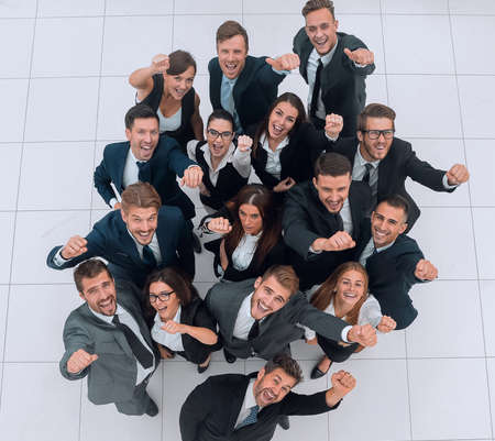 concept of success. business team raising hands and looking at camera.