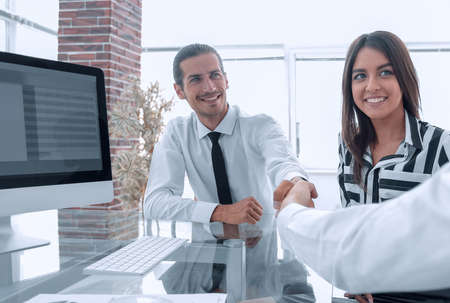 men shaking hands and smiling while sitting at the desk Stock Photo