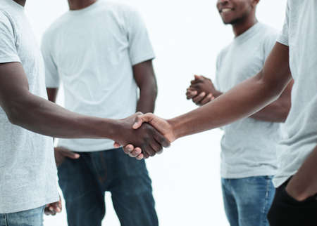 close up. smiling guys shaking hands. isolated on white background