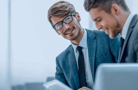 Two smiling elegant business people looking at something on digi