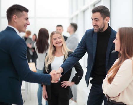 happy business people shaking hands with each other.