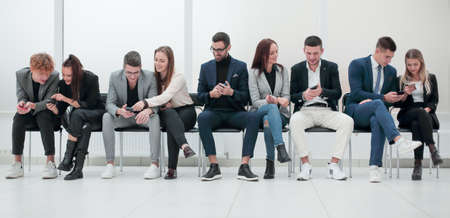 group of diverse young business people looking at their smartphone screens.
