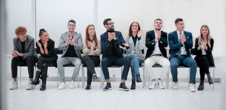 group of diverse business people applauding sitting in a row.
