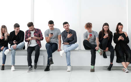 group of casual young people with smartphones sitting in a row.