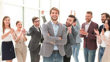 smiling entrepreneur on the background of jubilant business team