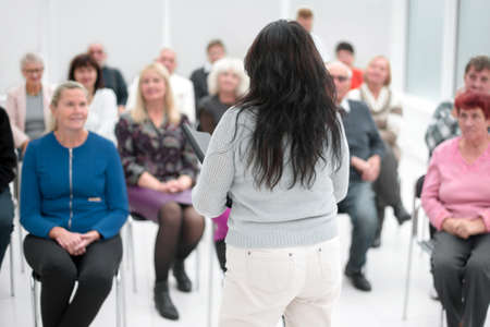 Rear view of Caucasian female speaker speaks to business people in a business seminar in a conference room Stock fotó