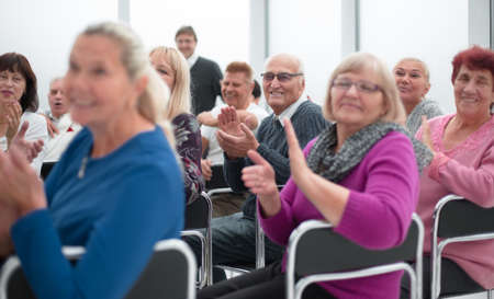 Audience of adult people listen to the speech of the lecturer applauding and smiling