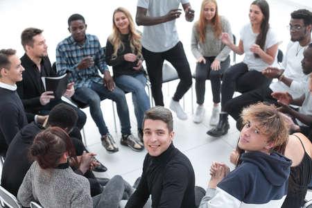 jeune homme souriant assis dans un cercle d'amis Banque d'images