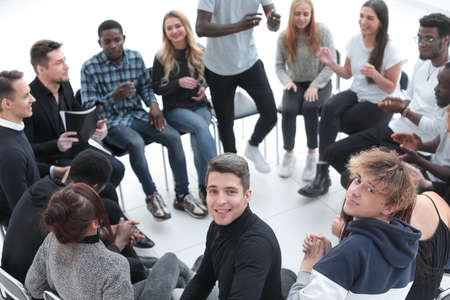 smiling young man sitting in a circle of friends Stock fotó