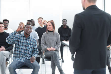 speaker and a group of diverse young listeners in a conference room Standard-Bild