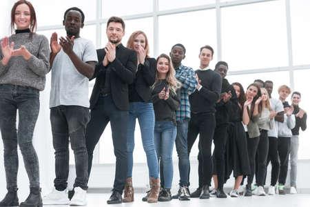 różnorodni młodzi ludzie biją brawo stojąc w kolejce