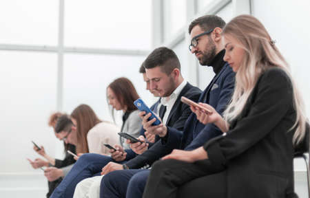 group of young business people with smartphones sitting in a row.