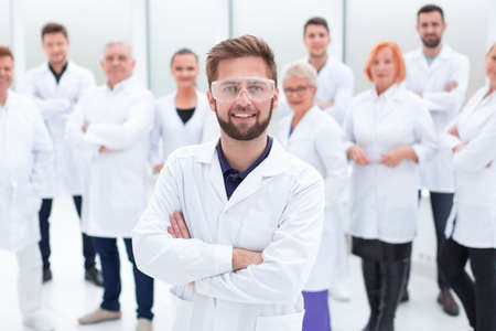 confident scientific leader standing in front of a team of young scientists.