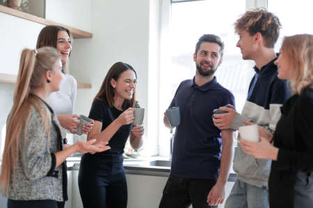 Friends holding tea cups clinking together in the kitchen