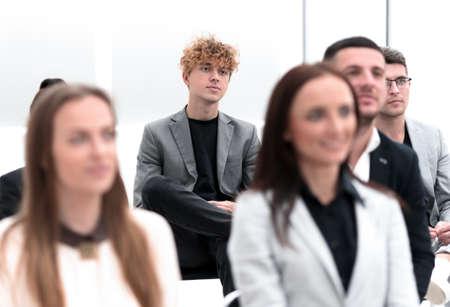 groupe d'employés assis dans une salle de conférence.