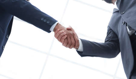 bottom view of two men shaking hands while standing