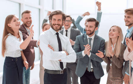 confident young businessman standing in front of a happy busines