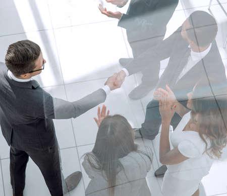 handshake business partners behind the glass door